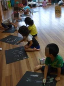 3才児クラスでは、黒の画用紙にチョークで絵を描いていました。