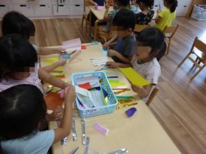 折り紙を細長く切っている女の子たち。 あとで輪っかにしてつなげるんだよ、と教えてくれました。