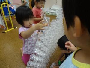 おやつのゼリーのカップを積んでいます。 手先も大分器用になって、集中して、そ~っと。