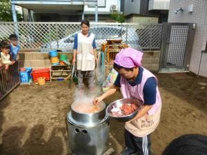 かまどでゆり組さんが切ってくれた大根とにんじんを煮ていたところへ、鮭を投入!
